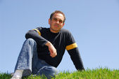 Man sitting on grass — Stock Photo