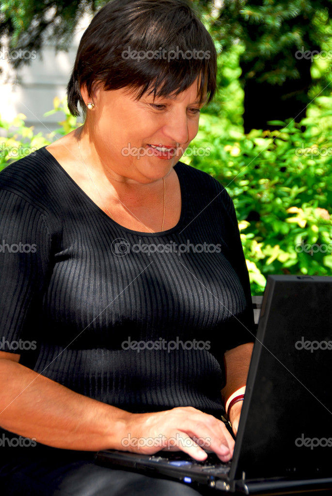 Mature woman working on laptop computer outdoors — Stock Photo #7636829