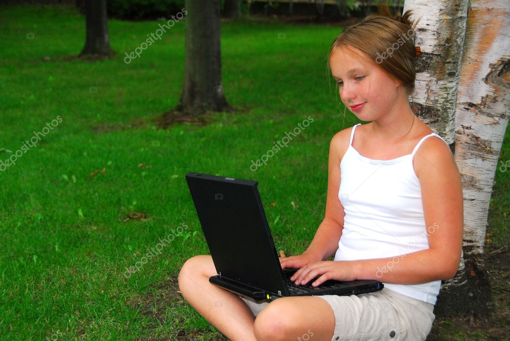 Young girl sitting in a park with laptop computer — Stock Photo #7638644