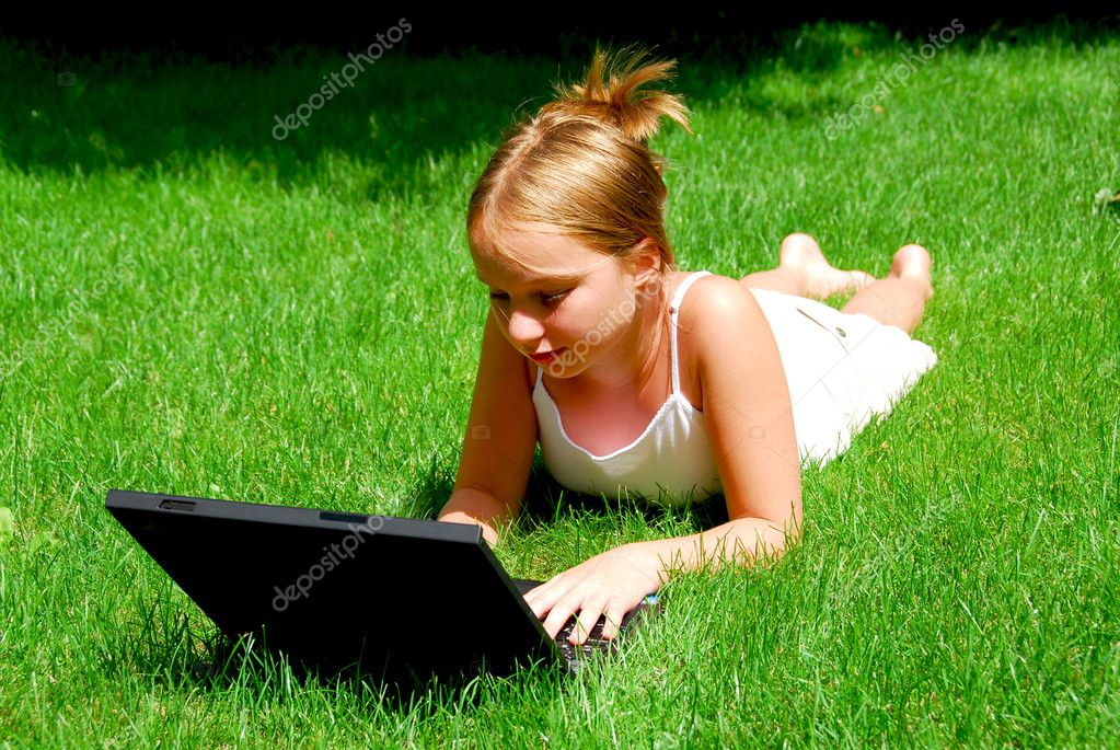 Young girl lying on grass in a park with laptop computer — Stock Photo #7638645
