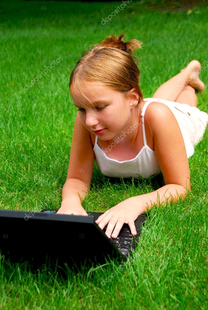 Young girl lying on grass in a park with laptop computer — Stock Photo #7638647