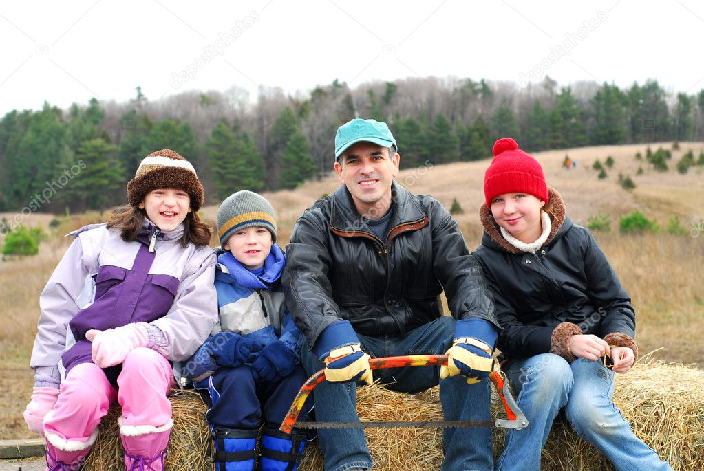 Family sitting on a vagon on Christmas tree farm — Stock Photo #7639193