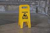 Yellow caution wet floor sign — Stock Photo