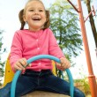 Cute little girl is swinging on see-saw — Stock Photo #6768253