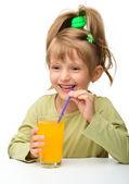 Cute little girl is drinking orange juice — Stock Photo