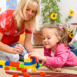 Teacher and child are playing with bricks — Stockfoto