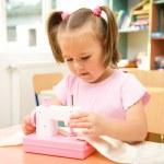 niña está jugando con la máquina de coser — Foto de Stock