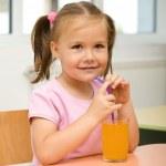 Little girl is drinking orange juice — Stock Photo