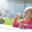 Little girl is blowing soap bubbles — Stock Photo