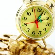 图库照片: Time is money - clock dial and golden coins