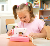 Little girl is playing with sewing machine — Stock Photo