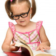 klein meisje is spiegelen over pagina's van een boek — Stockfoto