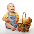 Cute little boy with basket full of vegetables — Stock Photo