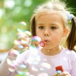 Little girl is blowing a soap bubbles — Stock Photo