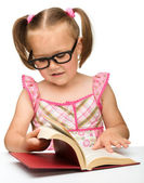 Little girl is flipping over pages of a book — Stock Photo