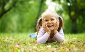 Little girl is playing in autumn park — Stock Photo