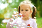 Little girl is blowing a soap bubbles — Fotografia Stock