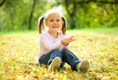 Little girl is sitting on green meadow — Stock Photo