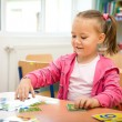 Cute little girl is playing with educational cards — Stock Photo #7180359