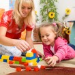 Teacher and child are playing with bricks - Stock Photo