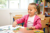 Cute little girl is playing with educational cards — Stock Photo