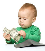 Cute little boy is counting money — Stock Photo