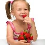 Happy little girl eats strawberries — Stock Photo #7415772