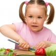 Little girl is cutting carrot for salad — Stock Photo #7446473