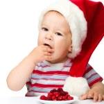 Cute little boy eating berries wearing santa hat — Stock Photo #7449728