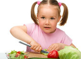 Little girl is cutting carrot for salad — Stock Photo