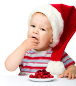 Cute little boy eating berries wearing santa hat — Stockfoto