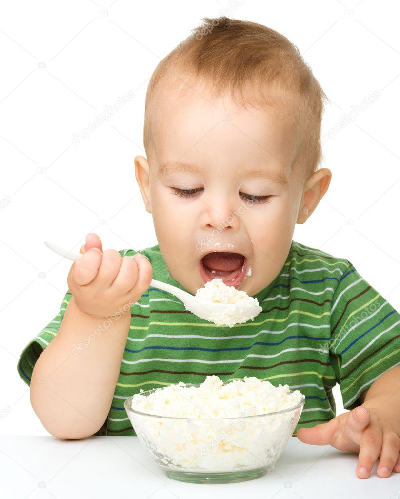 Little Boy Is Eating Cottage Cheese Using Spoon Stock