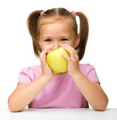 Little girl with yellow apple — Stock Photo