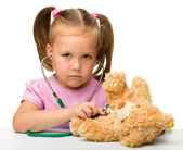 Little girl is playing with her teddy bear — Stockfoto