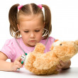 Little girl is playing with her teddy bear — Stok fotoğraf