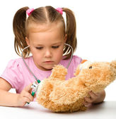 Little girl is playing with her teddy bear — Stock Photo