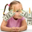 Cute little girl with paper money - dollars - Stock Photo