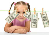Cute little girl with paper money - dollars — Stockfoto