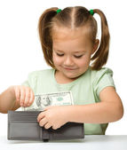 Cute little girl plays with money — Stock Photo