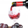 Red wine pouring in the goblet and grapes isolated in white — Stock Photo