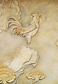 Golden relief of rooster — Stock Photo