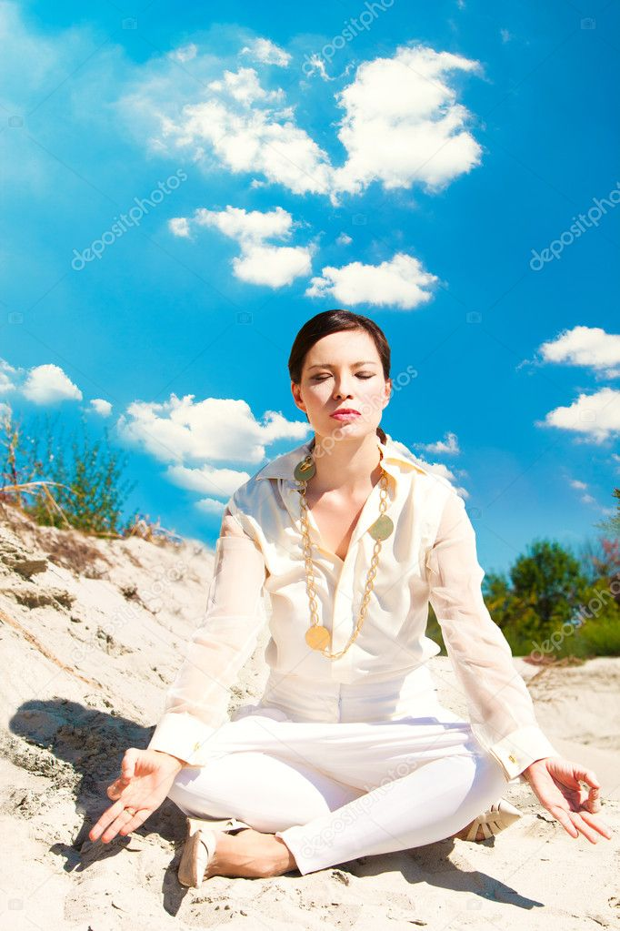 Adult woman in elegant light summer clothes meditate on sand, outdoor shot, summer day — Stock Photo #6763097