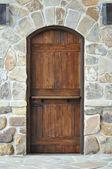 Wooden door on stone wall — Stock Photo