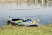 Old rowing boat moored on a river bank — Stock Photo