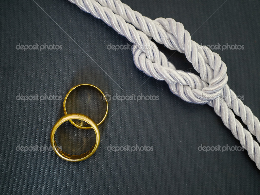 Silver Rope tie a knot and Two gold ring on black cloth — Stock Photo #6941874
