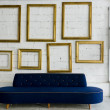 Long blue fabric sofa and gold picture frame — Stock Photo #7134396