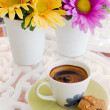 Ceramic cup of coffee with yellow and purple flower - Stok fotoğraf