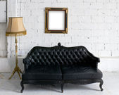 Old black leather sofa with lamp and wood picture frame — 图库照片