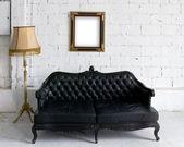 Velho sofá de couro preto com moldura de madeira e lâmpada — Foto Stock