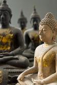 Bir beyaz taş buda ve üç siyah heykeli — Stok fotoğraf